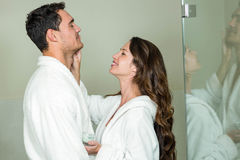 Woman applying moisturizer on man's face Royalty Free Stock Images