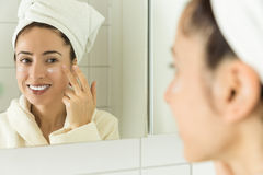 Woman applying moisturizer to her face Royalty Free Stock Images