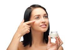 Woman applying moisturizing cream Royalty Free Stock Images