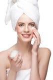 Woman applying moisturizing cream Stock Images