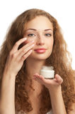 Woman applying moisturizing cream Stock Image