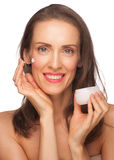 Woman applying moisturizing cream Royalty Free Stock Photography