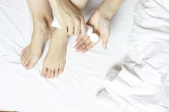 Woman applying moisturizing cream on her legs and feet in bedroom - body care concept stock image