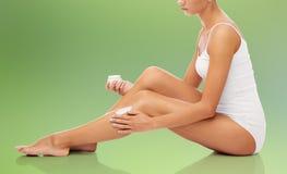 Woman applying moisturizing cream to her leg Stock Images