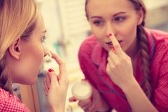 Woman applying moisturizing skin cream. Skincare. Young blonde woman applying moisturizing skin cream on face, looking in bathroom mirror. Girl taking care of Royalty Free Stock Photography
