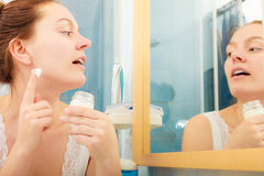 Woman applying moisturizing skin cream. Skincare. Young woman applying cleansing moisturizing skin cream on face. Girl taking care of dry complexion layering Stock Photo