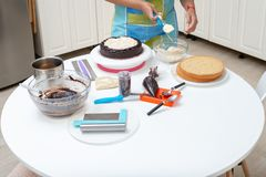 Woman applying mouse to a cake with cooking elements around stock photography