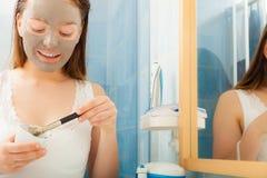 Woman applying mud facial mask Stock Photos