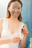 Woman applying mud facial mask Stock Images