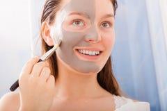 Woman applying mud facial mask Royalty Free Stock Photo