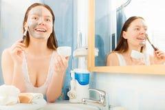 Woman applying mud facial mask Stock Photo