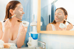 Woman applying mud facial mask Stock Image