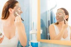 Woman applying mud facial mask Royalty Free Stock Image