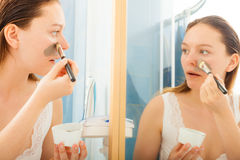 Woman applying mud facial mask Stock Photography