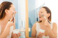 Woman applying mud facial mask Royalty Free Stock Images