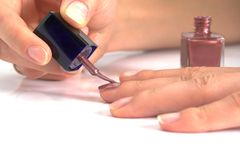 Woman applying nail enamel on Stock Photo