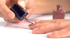 Woman applying nail enamel on. White background Stock Photo