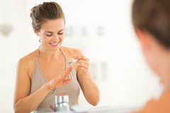 Woman applying nail polish in bathroom Stock Photography
