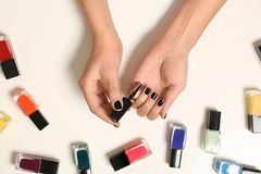 Woman applying nail polish near bottles on white background. Top view royalty free stock images