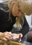 Woman applying nail varnish Royalty Free Stock Images
