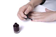 Woman applying nail varnish. Closeup on hands stock photos