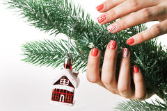 Woman applying nail varnish to finger nails and fir tree Royalty Free Stock Photography