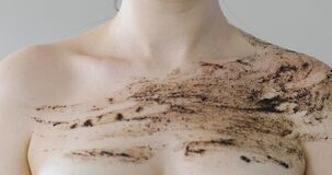 Woman applying organic coffee scrub on shoulder and chest, closeup front view.