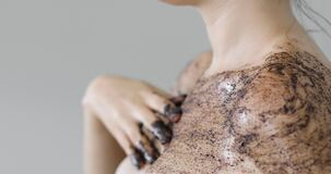 Woman is applying organic coffee scrub on shoulder and chest, closeup side view.
