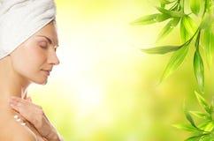 Woman applying organic cosmetics. Beautiful young woman applying organic cosmetics to her skin royalty free stock photo