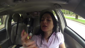 Woman applying perfume on her body while driving the car stock video footage