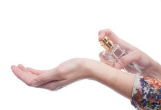 Woman applying perfume on her wrist, bright red pe Royalty Free Stock Image