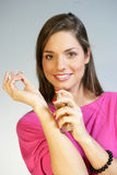 Woman applying perfurme on her wrist Royalty Free Stock Images