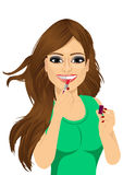 Woman applying pink lipstick on lips Stock Photo