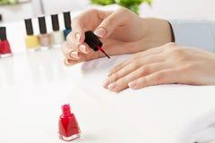Woman applying polish Stock Image