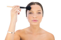 Woman applying powder brush on forehead Royalty Free Stock Photo