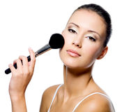 Woman applying powder on cheek with brush. Young beautiful woman applying powder on cheek with brush - isolated stock photo