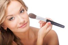 Woman applying powder on face Stock Photo