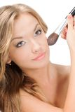 Woman applying powder on face Stock Images