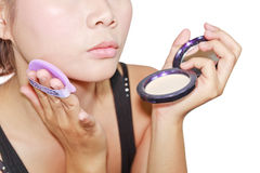Woman applying powder on face Royalty Free Stock Images