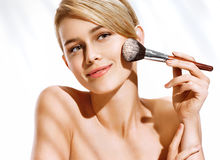 Woman applying powder on the face using makeup brush. Royalty Free Stock Images