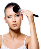 Woman applying powder on forehead with brush Royalty Free Stock Photography