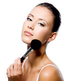 Woman applying powder on forehead with brush Stock Photo