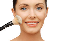 Woman applying powder foundation with brush Stock Images