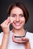 Woman applying powder on her skin Royalty Free Stock Image