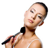 Woman applying powder on neck with brush Stock Image