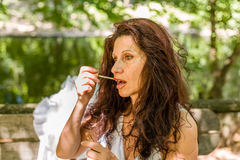Woman applying red glossy lipstick Stock Image