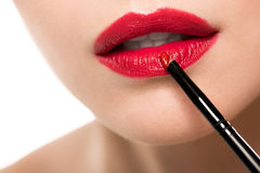 Woman applying red lipstick with brush Stock Images