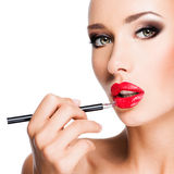 Woman applying red lipstick with cosmetic pencil on the lips Stock Image