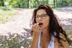 Woman applying red lipstick Stock Photography