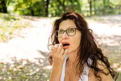 Woman applying red lipstick Stock Images